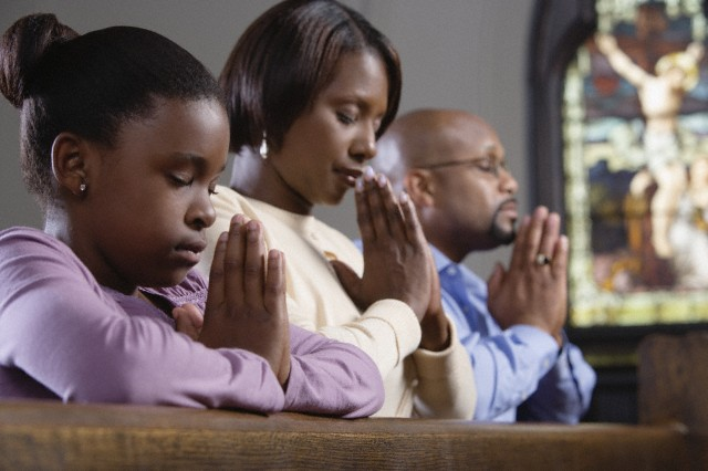 Family praying in church --- Image by © Ocean/Corbis